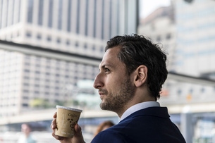 Young businessman in city with takeaway coffee, New York, USAの写真素材 [FYI03592551]