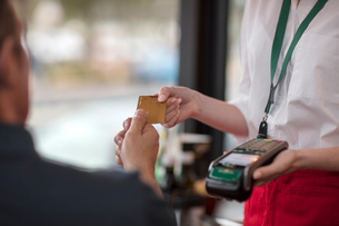Customer handing credit card to waitress for payment on card machineの写真素材 [FYI03593077]