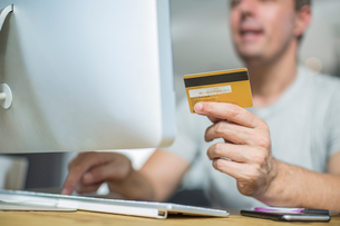 Cropped view of man holding credit card using computerの写真素材 [FYI03593082]
