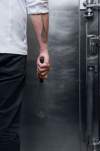 Cropped rear view shot of pastry chef with whisk tattoo holding whisk in kitchenの写真素材 [FYI03593119]
