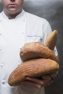 Cropped portrait of pastry chef holding loaves in kitchenの写真素材 [FYI03593122]