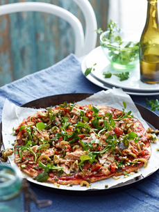 Tuna and green olive pizza on pizza dish, close-upの写真素材 [FYI03593235]
