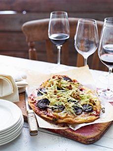 Blood sausage pizza on serving boardの写真素材 [FYI03593240]