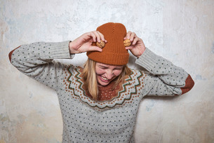 Portrait of woman wearing jumper and knitted hat, holding walnuts to her head, laughingの写真素材 [FYI03593314]