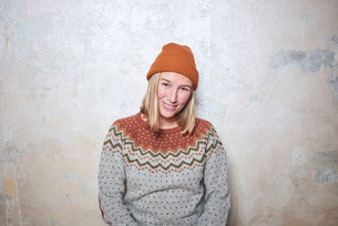 Portrait of woman wearing jumper and knitted hat, smilingの写真素材 [FYI03593318]