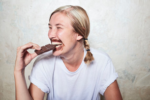 Woman eating bar of chocolate, chocolate around mouth, laughingの写真素材 [FYI03593319]