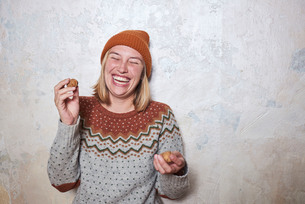 Portrait of woman wearing jumper and knitted hat, holding walnuts, laughingの写真素材 [FYI03593320]