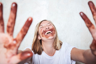 Portrait of woman with chocolate on hands and around mouth, holding hands towards camera, laughingの写真素材 [FYI03593323]