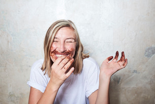 Portrait of woman with chocolate on hands and around mouth, laughingの写真素材 [FYI03593324]