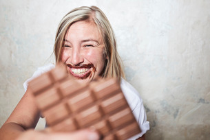 Portrait of woman eating bar of chocolate, chocolate around mouthの写真素材 [FYI03593325]