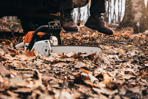 Man in boots and chainsaw on autumn forest floorの写真素材 [FYI03593492]