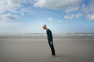 Boy standing on beach,leaning forward in the stormy wind, Gravelines, Nord-Pas-de-Calais, Franceの写真素材 [FYI03593533]