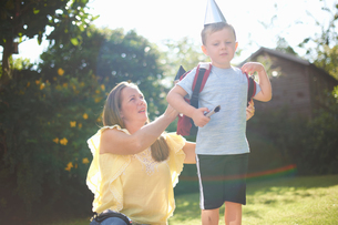 Mature woman putting rocket costume backpack onto son  in gardenの写真素材 [FYI03593551]