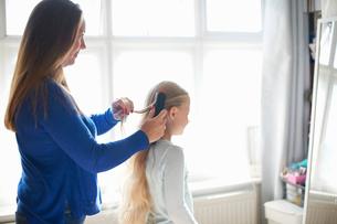 Mother brushing schoolgirl daughter's hair in bedroomの写真素材 [FYI03593560]
