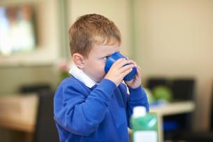 Schoolboy drinking juice in kitchenの写真素材 [FYI03593584]