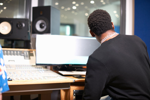 Rear view of young male college student at sound mixer in recording studioの写真素材 [FYI03593638]