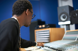Young male college student at sound mixer in recording studioの写真素材 [FYI03593639]