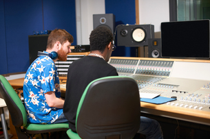 Two young male college students at sound mixer in recording studioの写真素材 [FYI03593642]