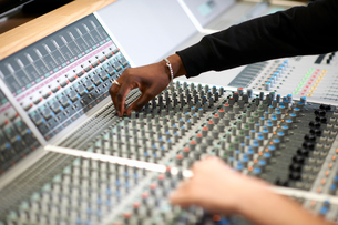 Hands of male college students at sound mixer in recording studioの写真素材 [FYI03593643]