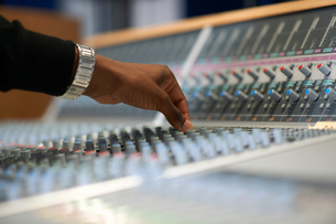 Hand of male college student at sound mixer in recording studioの写真素材 [FYI03593644]