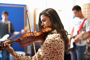 Young female college student playing violin in recording studioの写真素材 [FYI03593645]