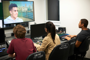 Young male and female college students at mixing desk watching TV screenの写真素材 [FYI03593667]