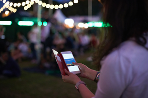 Mature woman reviewing smartphone photographs at night market festival in park, London, UKの写真素材 [FYI03593681]