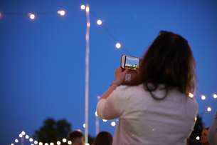 Mature woman photographing blue sky and lights at night market festival in park, London, UKの写真素材 [FYI03593682]