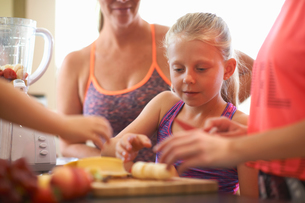 Girl and family preparing fruit for smoothie in kitchenの写真素材 [FYI03593683]