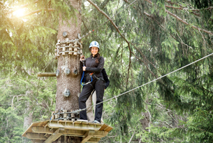 Teenage girl on high rope course looking at camera smilingの写真素材 [FYI03593772]