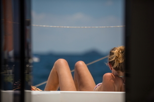 Rear view of woman sunbathing on yacht, Ban Koh Lanta, Krabi, Thailand, Asiaの写真素材 [FYI03594052]