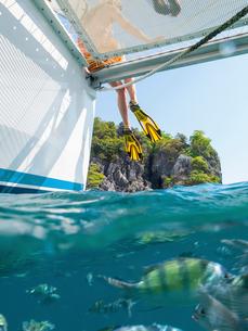 Legs of woman dangling from yacht, Koh Pak Ka, Krabi, Thailand, Asiaの写真素材 [FYI03594055]