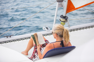 Rear view of woman relaxing on yacht, reading book, Ban Koh Lanta, Krabi, Thailand, Asiaの写真素材 [FYI03594063]