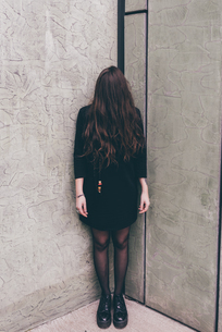 Portrait of young woman standing in corner, hair covering faceの写真素材 [FYI03594134]