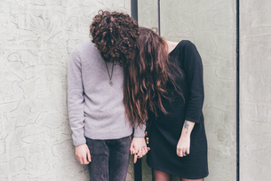 Young couple outdoors, standing against wall, holding hands, hair covering their faces,の写真素材 [FYI03594162]