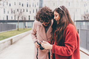 Young couple standing outdoors, looking at smartphone, laughingの写真素材 [FYI03594164]