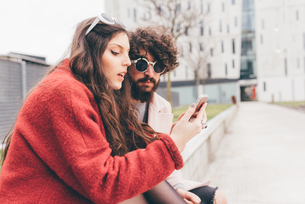 Young couple sitting outdoors, looking at smartphoneの写真素材 [FYI03594166]