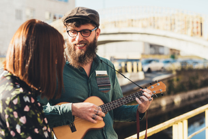 Hipster couple playing ukulele by canalの写真素材 [FYI03594224]