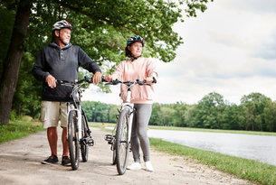 Mature couple walking along rural pathway with bicycles, looking at viewの写真素材 [FYI03594307]