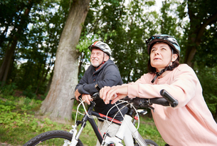 Mature couple walking along rural pathway with bicycles, looking at viewの写真素材 [FYI03594308]