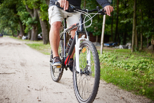 Senior man cycling along pathway, low sectionの写真素材 [FYI03594311]