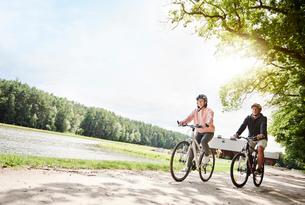 Mature couple cycling beside lakeの写真素材 [FYI03594312]