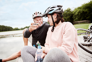 Mature couple relaxing on jetty, enjoying snack, bicycles behind themの写真素材 [FYI03594321]