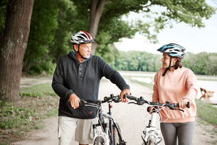 Mature couple walking along rural pathway with bicyclesの写真素材 [FYI03594324]