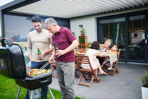 Mature and mid adult man barbecuing at family lunch on patioの写真素材 [FYI03594404]
