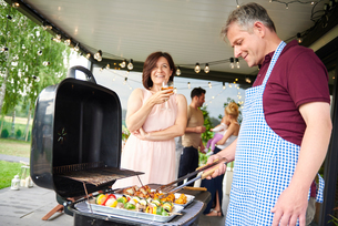 Mature couple barbecuing at family lunch on patioの写真素材 [FYI03594412]
