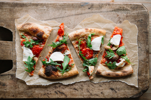 Pizza slices on chopping board, overhead viewの写真素材 [FYI03594558]
