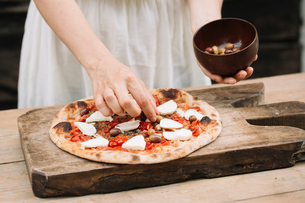 Woman putting olives on homemade pizza, mid sectionの写真素材 [FYI03594562]