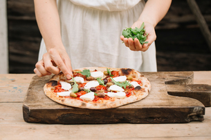 Woman putting herbs on home-made pizza, mid sectionの写真素材 [FYI03594565]