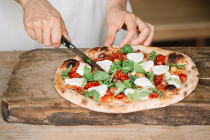 Woman cutting home-made pizza on chopping board, mid sectionの写真素材 [FYI03594571]